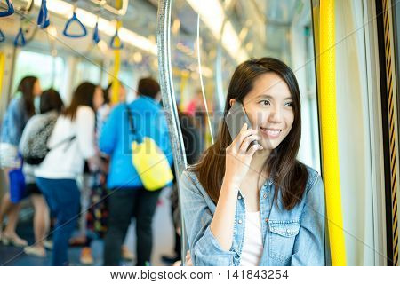 Woman talk to cellphone in train compartment