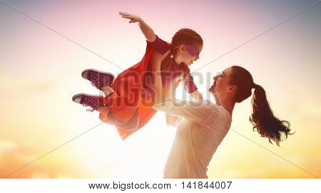 Mother and her child girl playing together. Kid in an Superhero's costume.