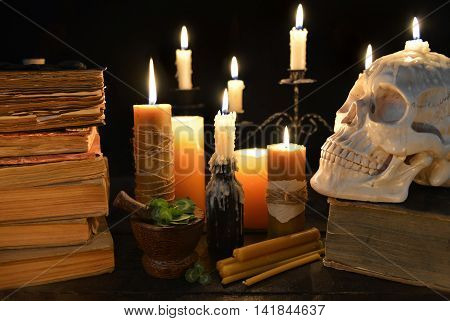 Halloween still life with burning candles, old book, clover and human skull on black