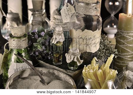Still life with bottles and healing herbs desaturated. Signs on bottles labels are not foreign text, these letters are imaginary, fictional symbols.