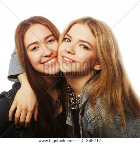 Two young girl friends standing together and having fun.Isolated on white.