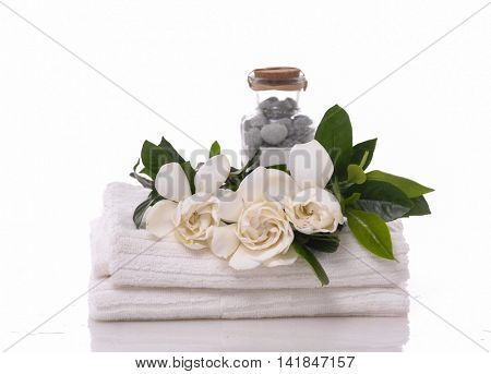 stones in bottle and gardenia on towel â??white background