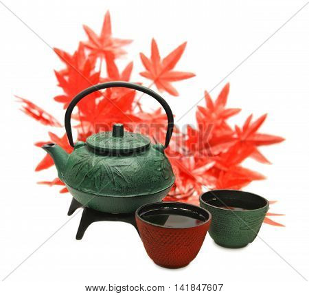 Green metal tea pot and two cups with tea against background of maple leaves, isolated objects