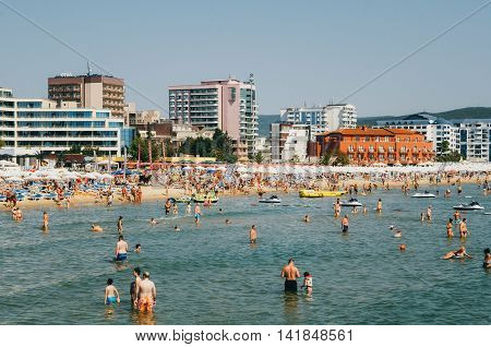 SUNNY BEACH BULGARIA - AUGUST 29 2015: A crowded beach scene at the central part of Sunny Beach in Bulgaria. A lot of people liing on the sunbeds and swimming in the sea