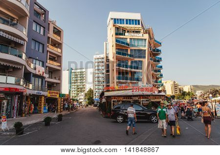 SUNNY BEACH BULGARIA - AUGUST 29 2015: Tourists walk along the promenade of Sunny Beach with numerous cafes bars restaurants and souvenirs shops.