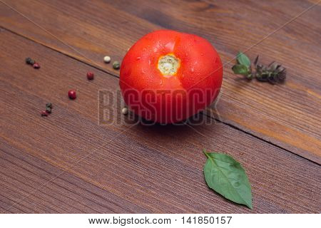 Red tomato pepper and basil leafs on wooden table