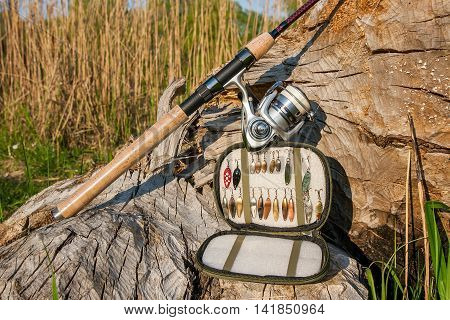 Fishing Rod With Reel And Various Kind Of Baits On The Natural Background.