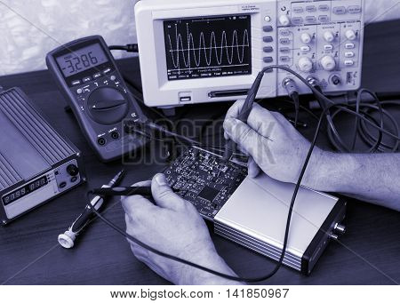 Engineer's hands holding probes and determining the voltage on the electronic contacts toned