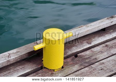 Yellow post for tying up boat on wooden platform