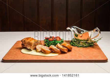 Osteria art of suckling pig porchetta on wooden cutting board