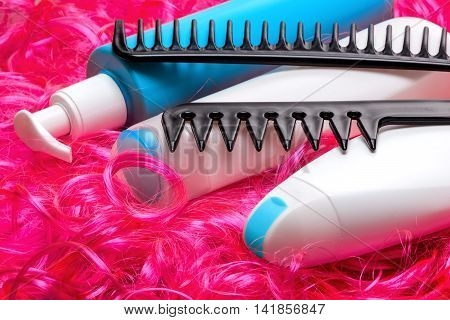 Curly hair care and styling products. Shampoo, conditioner, moisturizing oil for facilitate combing hair with wide tooth combs on bright pink doll hair