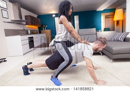 Young Couple Having Fun Doing Gymnastics At Home