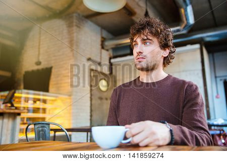Handsome attractive pensive curly thoughtful guy in brown sweetshirt drinking coffee sitting in cafe