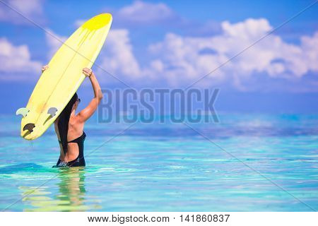 Beautiful surfer woman surfing in turquoise sea, on stand up paddle board at exotic vacation