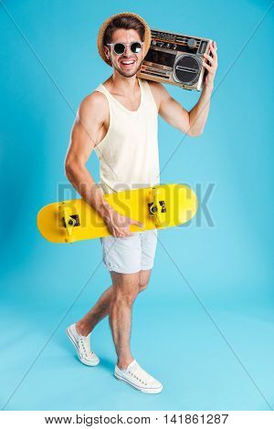 Smiling young man with yellow skateboard walking and holding old boombox over blue background