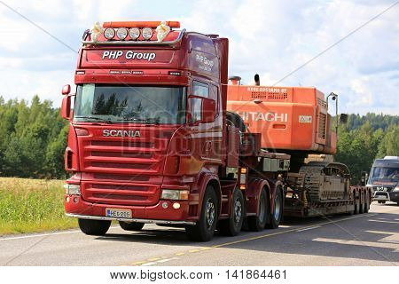 TENHOLA, FINLAND - JULY 30 2016: Red Scania semi truck transports large Hitachi Zaxis tracked excavator on noteboom trailer uphill along summer highway in South of Finland.