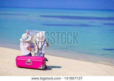 Little adorable girls with big colorful suitcase in hands walking on tropical beach