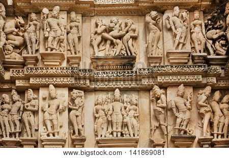 Stone relief with sexual life of ancient people on wall of Khajuraho temple, India. UNESCO Heritage site built between 950 and 1150 in India, belong to Hinduism and Jainism.