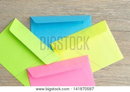Colorful envelopes displayed together on a wooden background