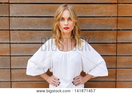 Young blonde woman with wavy hair and red lipstick in white blouse with hands akimbo