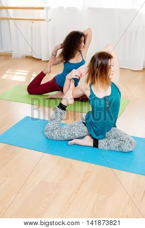 Two caucasian flexible young woman sitting in eka pada rajakapotasana asana in yoga studio