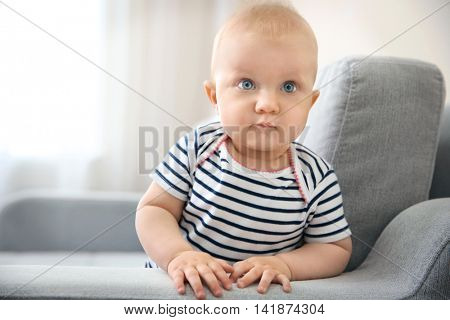 Adorable little baby crawling on light sofa