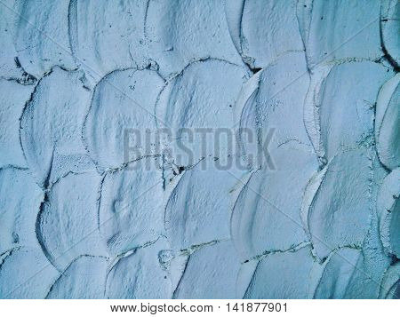blueish fish-like scale pattern on rough cement wall