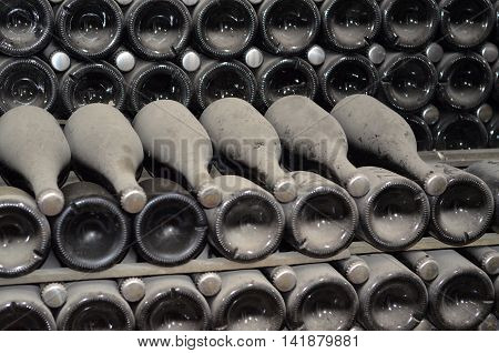 Maturing in dusty champagne bottles in wine cellars of  factory of sparkling wines, focus at top