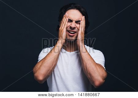 Oh no! Worried young man covering face with hand while standing against grey background