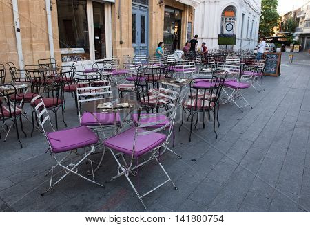 Nicosia Cyprus - July 18 2016: People sitting in a coffee shop with vintage Chairs and tables outside cafe in the streets of the town of Nicosia in Cyprus.
