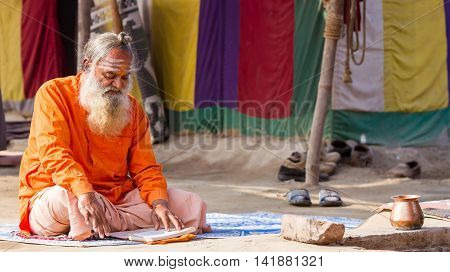 ALLAHABAD INDIA - FEB 13 - A Hindu priest studies scriptures in front of his tent during the festival of Kumbha Mela on February 13th 2013 at Allahabad India.