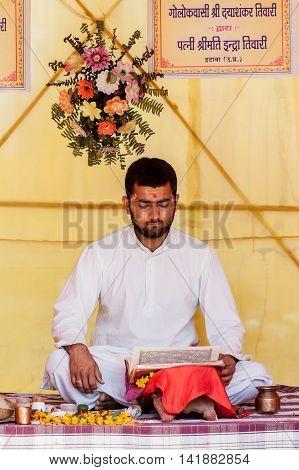 ALLAHADBAD, INDIA - 14th Feb 2013 - A pundit reads from Hindu scriptures at the Kumbha Mela