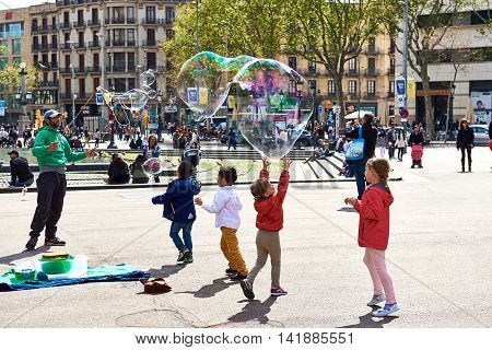 Barcelona Spain - April 3 2016: Children catching the soap bubbles in the Catalonia Square (Plaza de Cataluna) is a large square in central Barcelona. Spain