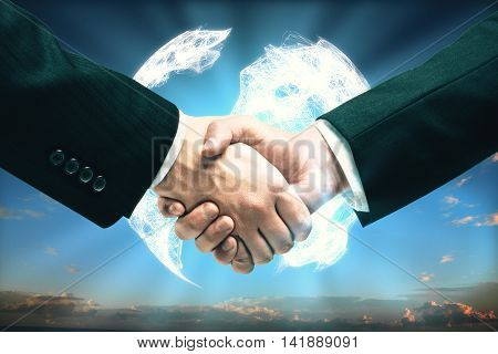People shaking hands in front of digital terrestrial globe on sky background. Global business concept