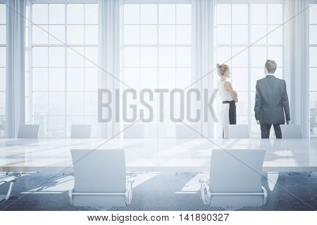 Two businesspeople in bright conference room interior with blurry city view and daylight. 3D Rendering