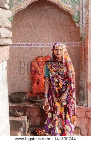 VARANASI, INDIA - FEB 18 - An old Hindu lady worships Hanuman, the monkey god, at a temple in Varanasi on February 18th 2013