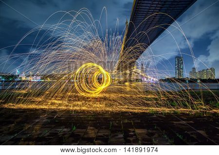 Hot Golden Sparks Flying From Man Spinning Burning Steel Wool Under Bhumibol Bridge In Bangkok Thail