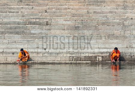 VARANASI, INDIA - FEB 19 - Two sadhus sit on the ghats overlooking he Ganges river at Varanasi on February 19th 2013