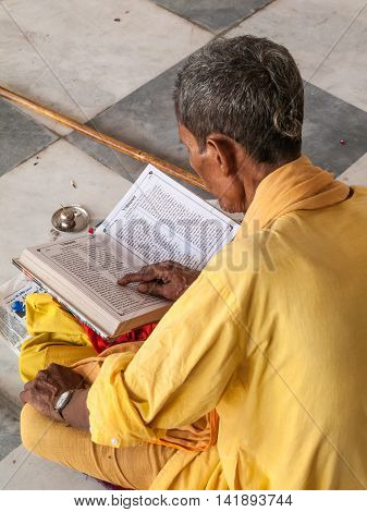 VRINDAVAN, INDIA - OCT 3rd - An old sadhu reading sacred texts in a Krishna temple in Vrindavan on October 3rd 2009