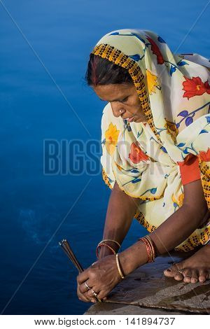 VRINDAVAN, INDIA - AUG 18th - A women offering prayers and incense on the banks of a river.