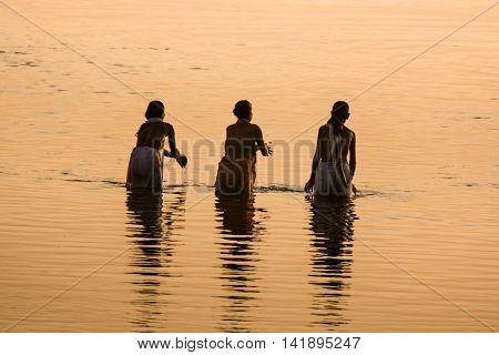 10th October 2009 - Vrindavan - Three women bathing and offering prayers in a holy river.