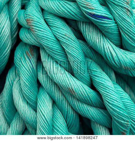 Nautical background. Old blue frayed ship rope closeup.