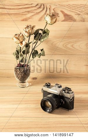 Old Vintage Camera And Rose Dry On Wooden Background.