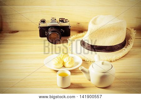 Relaxing afternoon drinking tea with eclair cream sweets on wooden table. sepia style image.