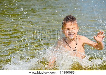 Boy swims in the lake water with a green tint