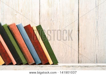 Books Wood Shelf Old Spines Covers on White Vintage Wooden Wall