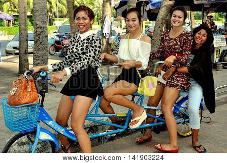 Bang Saen Thailand - January 7 2014: Four Thai girls riding along the beach promenade on a bicycle built for three