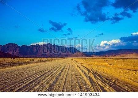 Travel to Namibia. The dirt road in Namib-Naukluft national park goes to distant mountains. Ecotourism in Africa