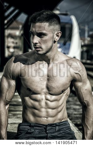 Portrait of young shirtless man with sexy body posing on train railway while looking down