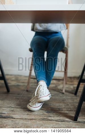 Close up of female legs with shoes under wooden table.